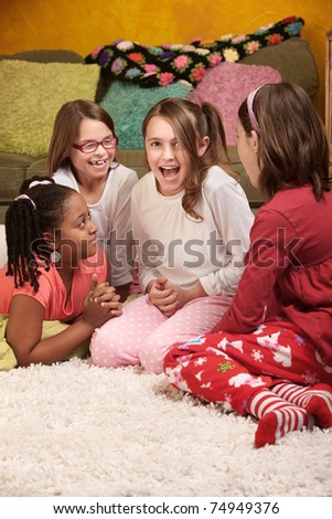 Four happy little girls sharing stories at a sleepover - stock photo