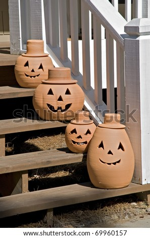 Four happy pumpkins on steps to a house.