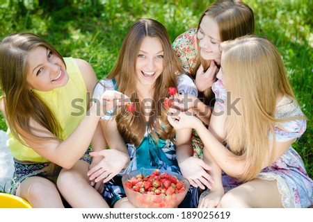 Four happy smiling beautiful group of young women teenagers having good time & fun eating strawberry on summer green outdoors background - stock photo