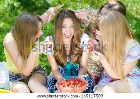 Four happy smiling & some looking at camera teenagers with red strawberry on summer green outdoors background - stock photo