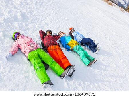 Four happy snowboarders lying in a row