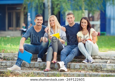 Four happy students sitting outdoors in university campus - stock photo