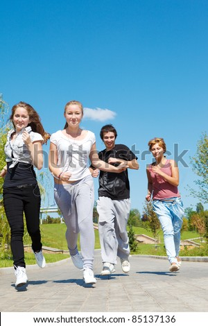Four happy teen friends running - stock photo