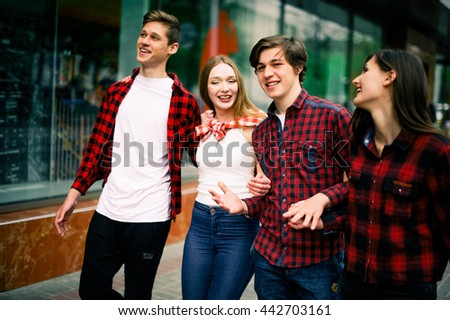 Four happy trendy teenage friends walking in the city, talking each other and smiling. Lifestyle, friendship and urban life concepts. - stock photo