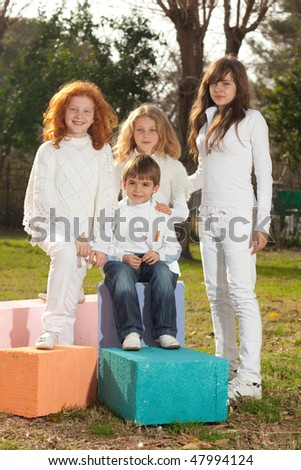 Four happy young children including twins with white clothes sitting on colorful cubes, sun reflection in hair, back-light