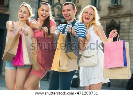 Four happy young persons looking satisfied after shopping with few paper bags in city