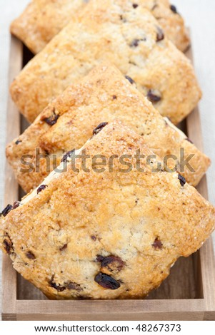 Four home baked scones in a wooden tray - stock photo