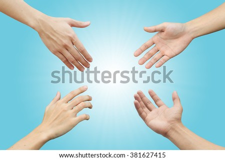 four human hands try to reaching on blur blue teal color background with sun rays: collaborate working together concept:love,trust,hope of humanity idea:helping hands conceptual - stock photo