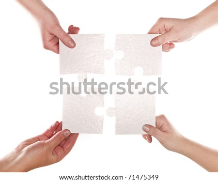 Four human hands with puzzle pieces connecting - stock photo