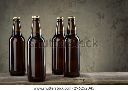 Four ice cold beer bottles in a row over the grey concrete wall background - stock photo