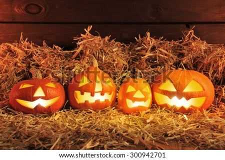 four illuminated halloween pumpkins and straw in front of old weathered wooden board in red light - stock photo