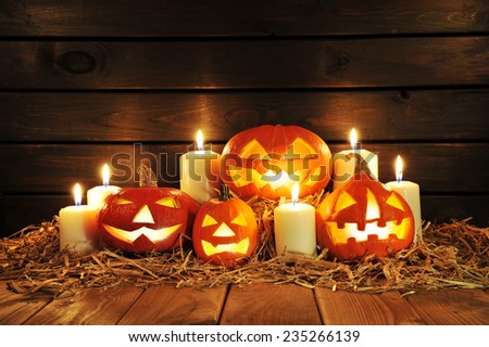 four illuminated halloween pumpkins with candles on straw in front of old weathered wooden board in candlelight - stock photo