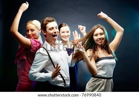 Four joyful friends dancing together - stock photo