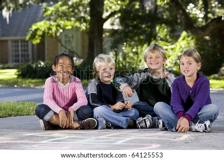 Four kids ages 7 to 9 sitting together in a row on driveway outside house - stock photo