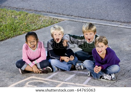 Four kids ages 7 to 9 sitting together on drive laughing and shouting - stock photo