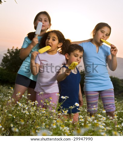 four kids having Popsicle in a summer sunset - stock photo