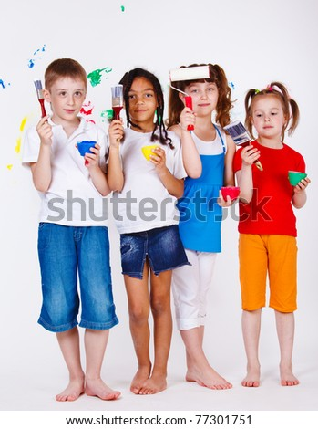 Four kids holding paintbrushes and paints in hands - stock photo