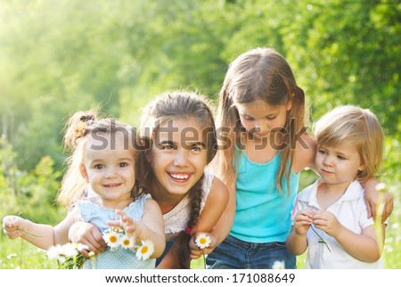 Four kids running in the daisy spring field - stock photo