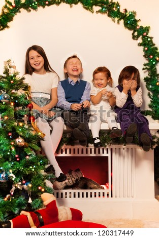 Four kids sitting on the fire place with Christmas tree close to them - stock photo