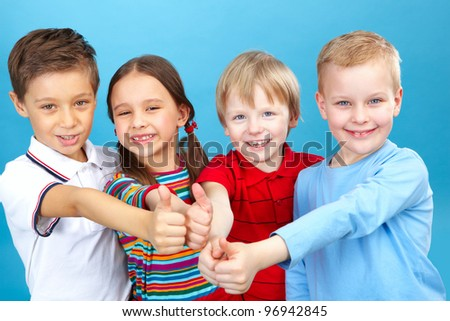 Four kids with their thumbs up looking at camera - stock photo