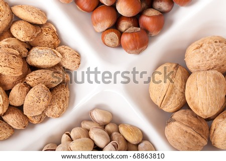 Four kinds of nuts lie on a plate on a white background. Focus in the shot center. - stock photo