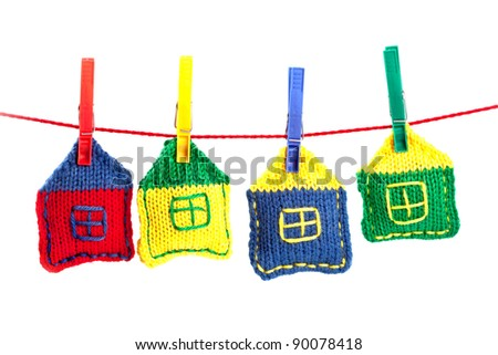 four knitted colorful houses on a red string isolated on white background - stock photo