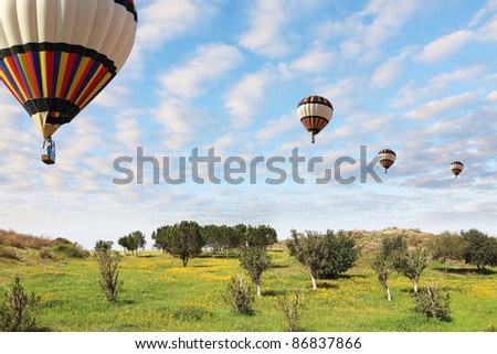 Four large bright balloons with a passenger basket fly by over spring blossoming fields - stock photo