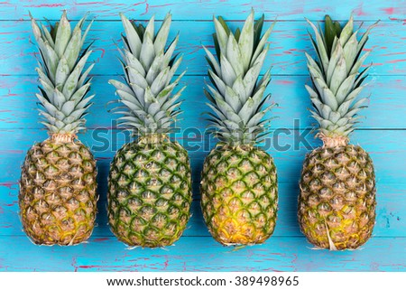 Four large ripe pineapple fruits arranged next to each other on old blue wooden plank table or floor background - stock photo