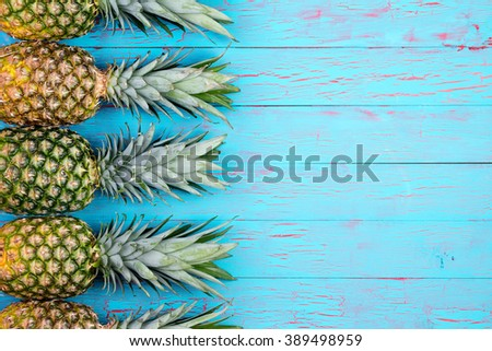 Four large ripe pineapples neatly arranged in row with copy space over wooden background in tropical theme - stock photo