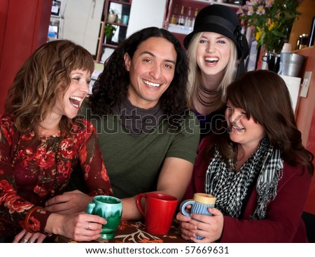 Four laughing friends enjoying coffee in a cafe - stock photo