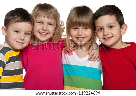 Four laughing kids are standing together; isolated on the white background - stock photo