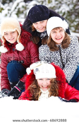Four laughing teenage girls in a snowy park