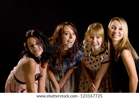 Four laughing teenage girls in stylish outfits having fun leaning forwards together with mischievous smiles on a dark studio background - stock photo