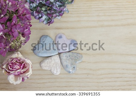 four leaf clover figured with soap stone hearts and dried blossoms on wooden background - stock photo