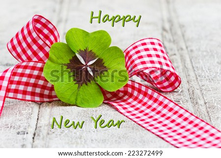 four leaf clover with checkered ribbon on wood, Happy New Year - stock photo