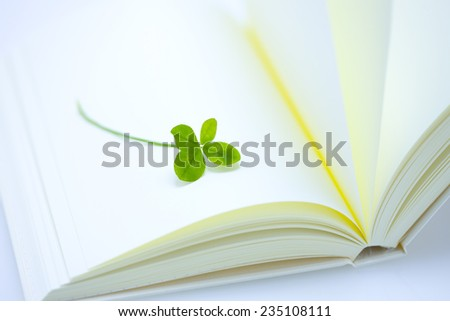 Four leaves and blank book - stock photo