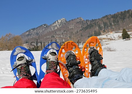 Four legs with snowshoes for excursions on the snow in the mountains - stock photo