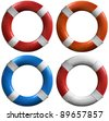 Four life buoys of various colors: red and white, orange and white, blue and white - stock photo