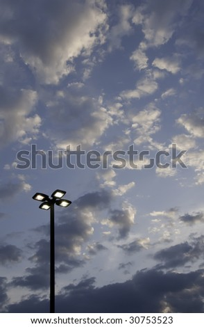 Four lights on pole in silhouette at sunset