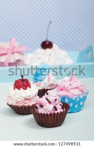 Four little baby blue and pink decoration cupcakes with chocolate sprinkles and whipped cream - stock photo