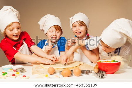 Four little bakers using cookie cutters