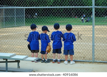 four little boys wait for their baseball game to begin - stock photo