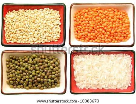 Four little dishes, each one full of two types of rice (moti and carolina gold), red lentils and  green-mung  beans on a white background. It has a clipping path. - stock photo