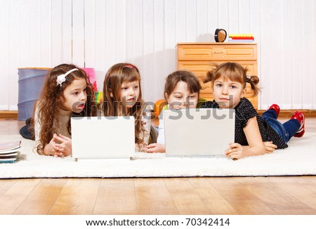 Four little friends lying on the floor with laptops - stock photo