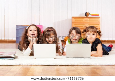 Four little friends with two laptops - stock photo