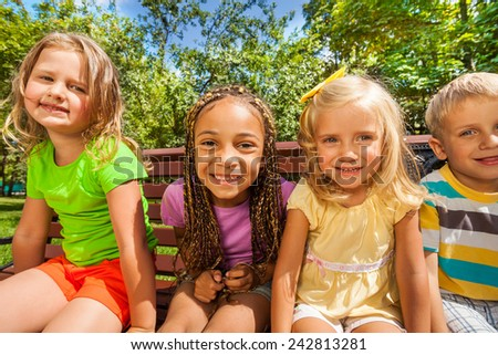 Four little kids happy and smiling sitting on the bench and looking close to wide angle lens with funny smiling faces - stock photo