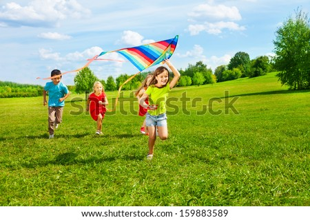 Four little kids running in the park with kite happy and smiling - stock photo
