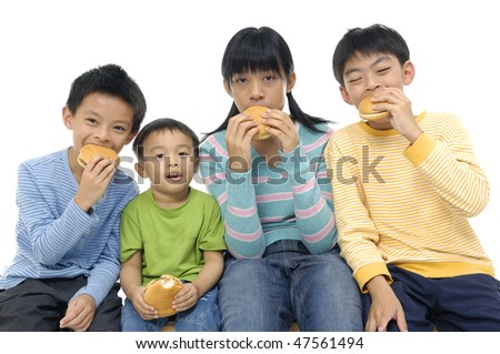 Four little young friends eating hamburgers - stock photo