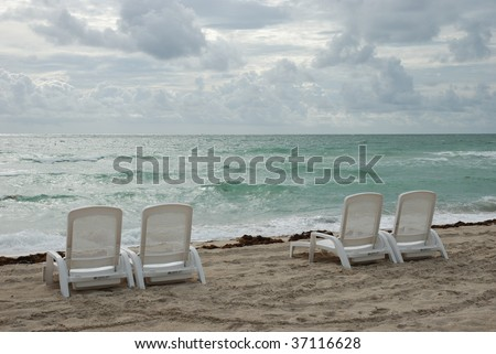 Four lonely chairs in rough weather at the shoreline in Florida - stock photo