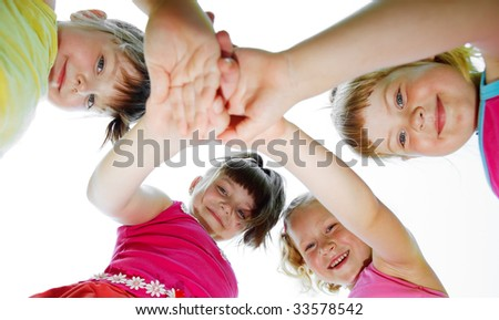 Four lovely girls putting hands of friendship one on another - stock photo
